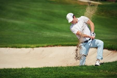 24914919 - golf shot from sand bunker golfer hitting ball from hazard